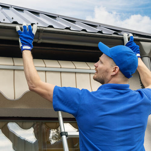A Roofer Installs a Section of Gutter on a Home