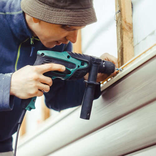 A Construction Worker Installs Siding.